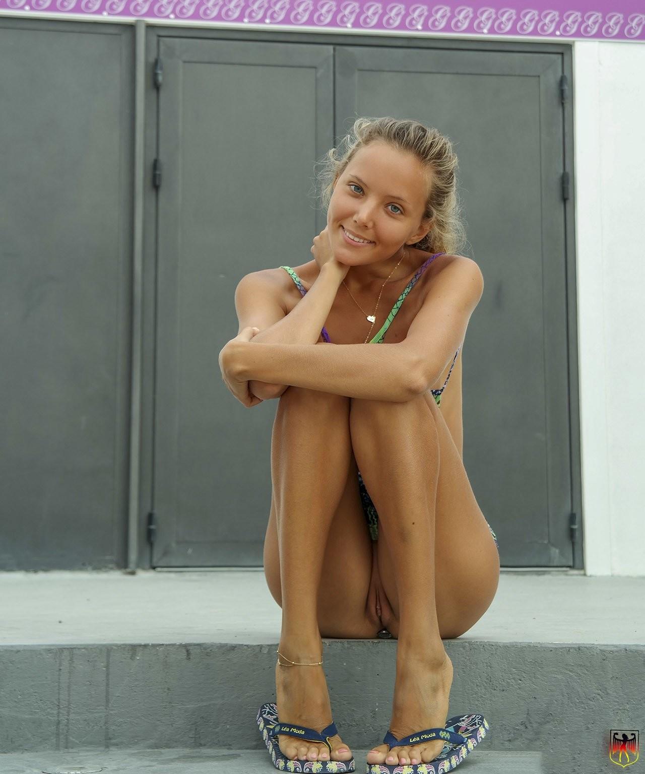 Эротичное позирование у дороги симпатичной девки в короткой юбке, без трусиков и с пробкой в попе